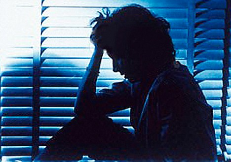 Silhouette of woman sitting in a dim room